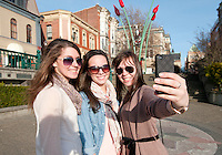 Three young women smile for the camera as they enjoy sightseeing near Bastion Square in downtown Victoria, BC Canada.