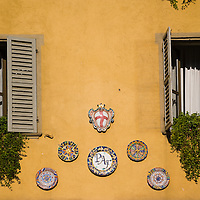 Windows and dishes on apartment building facade, Cherasco, Piedmont, Italy