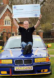 Neil Trotter a  car mechanic and racing driver from Coulsdon, United Kingdom celebrates on the bonnet of a racing car at a hotel in Dorking, United Kingdom, after winning the £108 million (pounds sterling) EuroMilllions lottery, Tuesday, 18th March 2014. Picture by Stephen Lock / i-Images