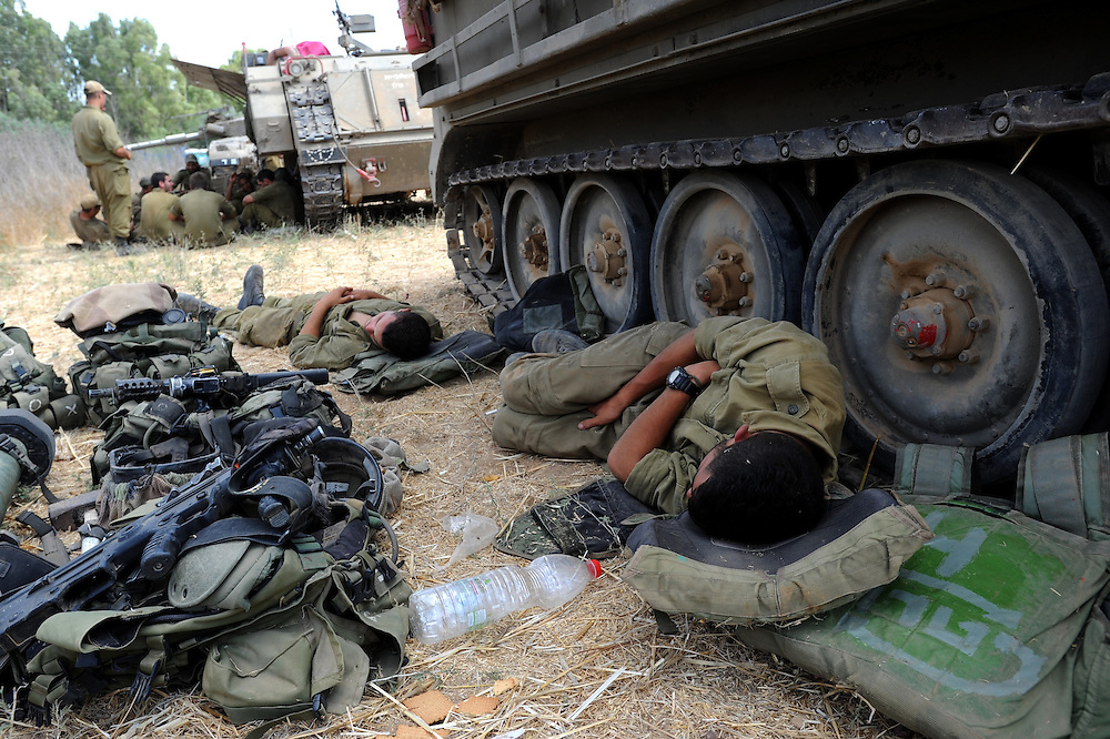 UNSPECIFIED, ISRAEL - JULY 19, 2014: Israeli soldiers sleep next to an APC in an army deployment area near Israel's border with the Gaza Strip, on July 19, 2014,  on the second day of Israeli ground invasion into Gaza Strip in order to destroy terror tunnels infrastructure. Photo by Gili Yaari
