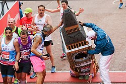© Licensed to London News Pictures. 28/04/2019. London, UK.  A man dressed in Big Ben struggles at the finish of 2019 Virgin Money London Marathon. Photo credit: Dinendra Haria/LNP