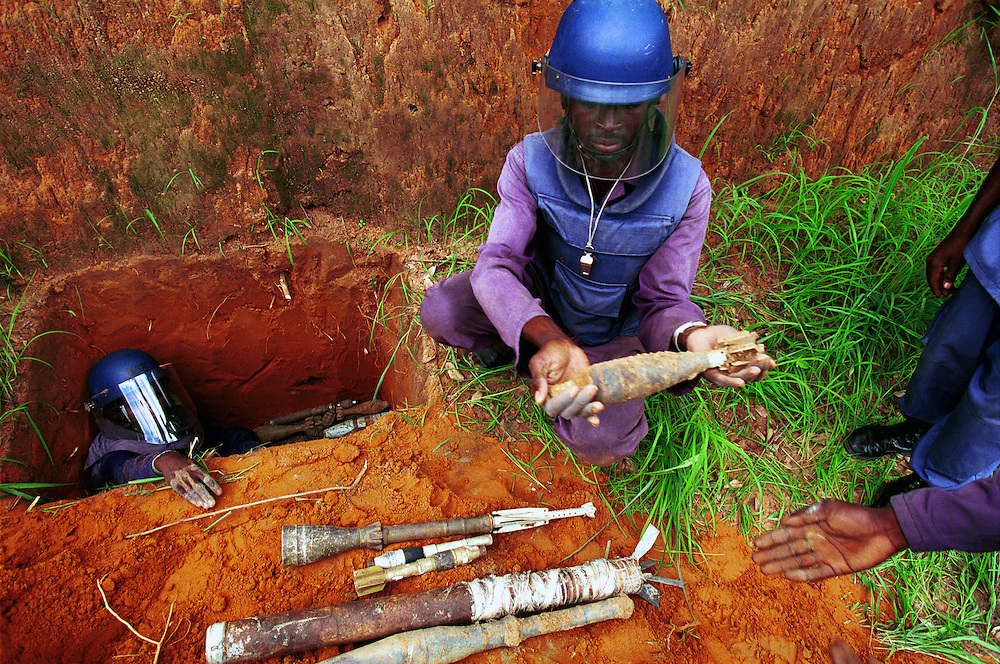 MAG (Mines Advisory Group) deminers prepare a controlled demolition of cleared land mines and unexploded ordinance.  Decades of civil war between government FAA (Fora Armada Angolana) forces and Jonas Savimbi's rebel army have littered Angola with landmines and UXOs, crippling and impoverishing the population. .Luena, Angola.  24-11-2001.Photo: J.B. Russell