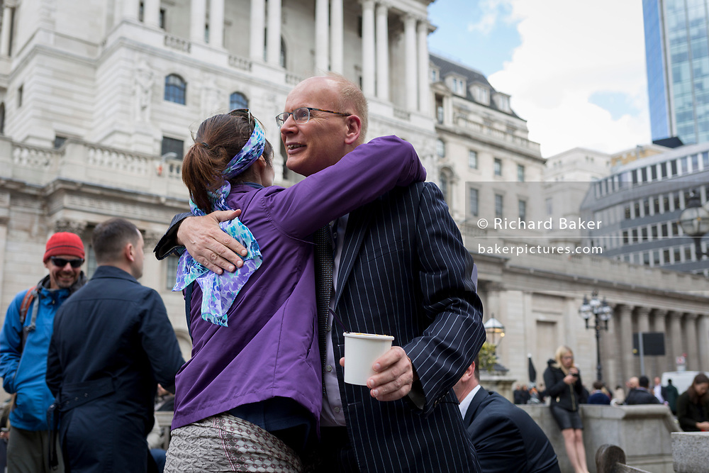 An environmental protester and a businessman hug after debating climate change and big business while having his lunch beneath the Bank of England in the City of London on the 11th and final day of protests, road-blockages and arrests across London by the climate change campaign Extinction Rebellion, on 25th April 2019, in London, England.