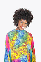 Portrait of an attractive African American woman in multicolored dashiki standing over gray background