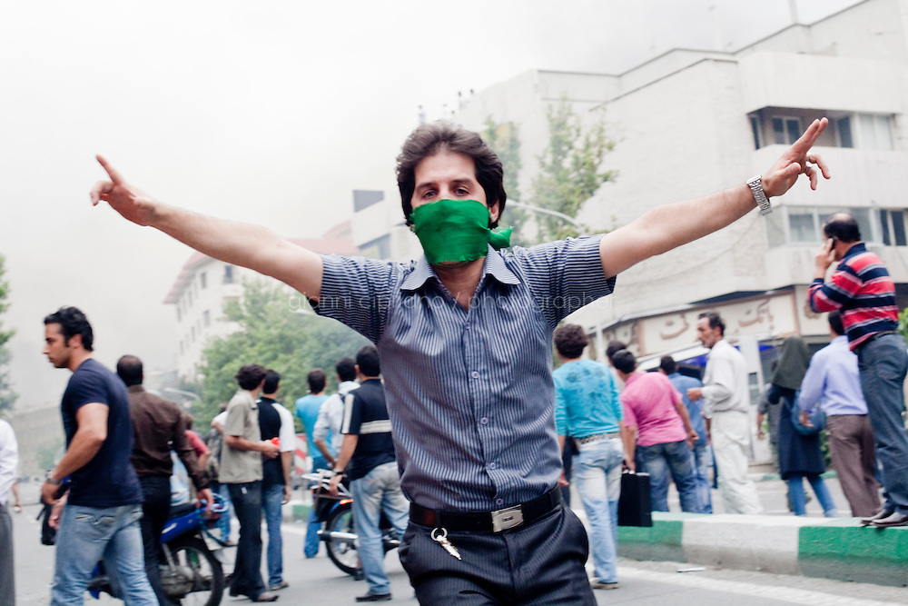 13 June, 2009. Tehran, Iran. A supporter of reformist candidate Mir Hosseing Moussavi runs and waves the peace sign as the riot police is about to fire tear gas on the crowd. Police clamped down on supporters of the opposition candidate, Mir Hussein Moussavi, who said the election was stolen by President Ahmadinejad. Conservative reformist candidate Mir Hossein Mousavi ran against the ultra-conservative current President of Iran Mahmoud Ahmadinejad.<br /> &copy;2009 Gianni Cipriano<br /> cell. +1 646 465 2168 (USA)<br /> cell. +39 328 567 7923<br /> gianni@giannicipriano.com<br /> www.giannicipriano.com