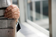 businessman reading his newspaper while waiting at the airport