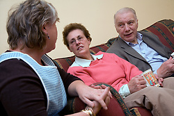 Carer talking older couple at home,