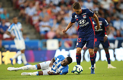 Huddersfield Town's Adama Diakhaby (left) and Lyon's Maxence Caqueret battle for the ball during a pre-season friendly match at the Kirklees Stadium, Huddersfield.
