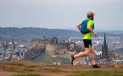 Edinburgh, Scotland, UK. 5 April, 2020. On the second Sunday of the coronavirus lockdown in the UK the public are outside taking their daily exercise. A man running on Salisbury Crags in Holyrood Park with Edinburgh Castle in distance. Iain Masterton/Alamy Live News