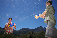 Two teenage boys (16-17 years) fighting with squirt guns in mountains