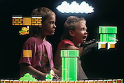 Virtual reality videogame: Evan & Jack Menzel appear to do battle over who is to wear the Nintendo Power Glove to interact with the fictional (or virtual) Super Mario Brothers (Nintendo characters) in the living room of their home in Napa, California. Model Released (1990)