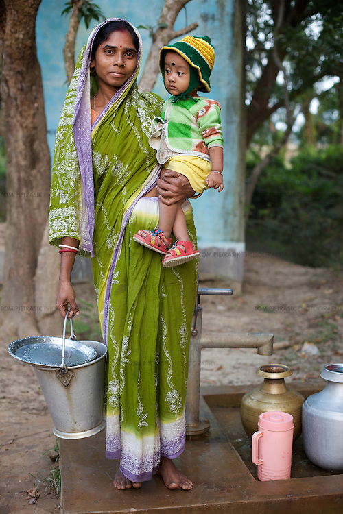 A woman and her child from Podumkhana village collects water from a TARA pump.  This pump was provided by UNICEF. The community is responsible for the monitoring of water quality and maintenance of the pump. The pump has a committee who fund quality control and maintenance by levying a charge of INR1 per month for each household that uses the pump. UNICEF through its partners the Ramakrishn Mission has provided training for local women so that they can undertake minor maintenance repairs to the pump and has also provided them the tools for this maintenance. The Ramakrishna Mission has provided TARA pump maintenance training for 143 groups in Purbamedinipur district. Using the local media, UNICEF have also undertaken awareness drives in this area to encourage the community to make use of water pumps and latrines. Podumkhana village has three water pumps for 238 households but suffers from poor water supply in the summer months. <br /> <br /> Photo: Tom Pietrasik<br /> Podumkhana village, Purbamedinipur district, West Bengal. India<br /> October 25th 2009