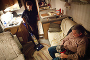 Sarann Williams, left, vacuums around her husband Ray Williams in the RV they share while working a seasonal job at an Amazon warehouse in Fernley, Nevada, December 13, 2011. CREDIT: Max Whittaker/Prime for The Wall Street Journal.AMAZONTOWN