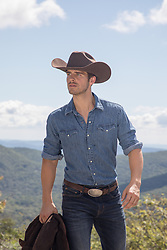 hot cowboy by a mountain range