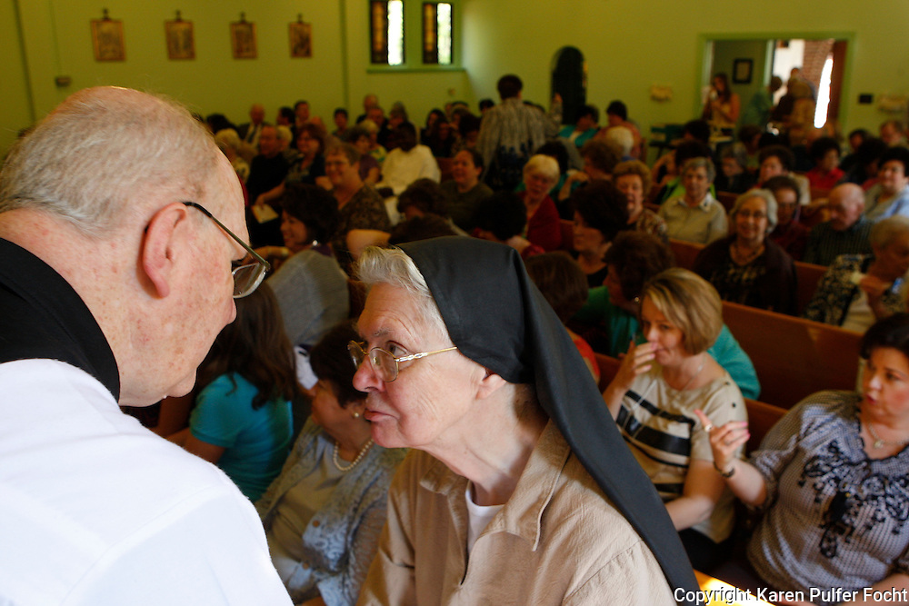 Sister John, an aging cloistered Poor Clare Nun from Memphis, Tennessee,  speaks with Father James Pugh. The number of Poor Clare nuns in Memphis is dwindling. They are a community of Catholic women who have chosen to embrace the way of life proposed by a young Italian girl in Assisi over 800 years ago.