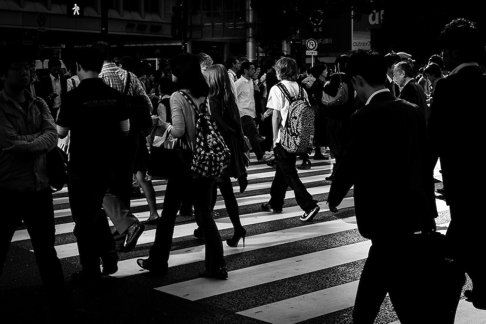 A kid crosses the street mingling with other pedestrians on the famous Shibuya Station zebra crossings