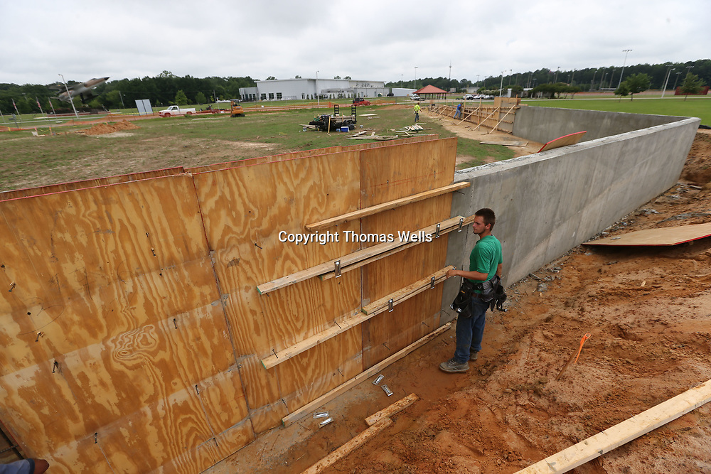 Kolby Cleveland secures the  wooden forms so they can pour the concrete to complete the new Vietnam Wall memorial under construction at Veterans Park on Tupelo.