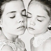 Close upof two young girls with their heads together and eyes closed