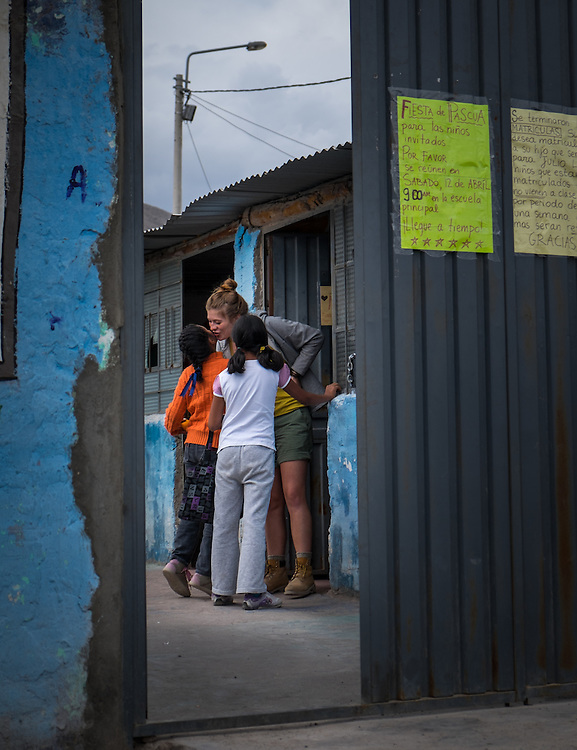 AREQUIPA, PERU - APRIL 7, 2014: Volunteer teacher welcoming student in the community of Flora Tristan for HOOP Peru. HOOP Peru is a NGO fully committed to breaking the cycle of poverty by empowering the Flora Tristan families through enhancing their education.