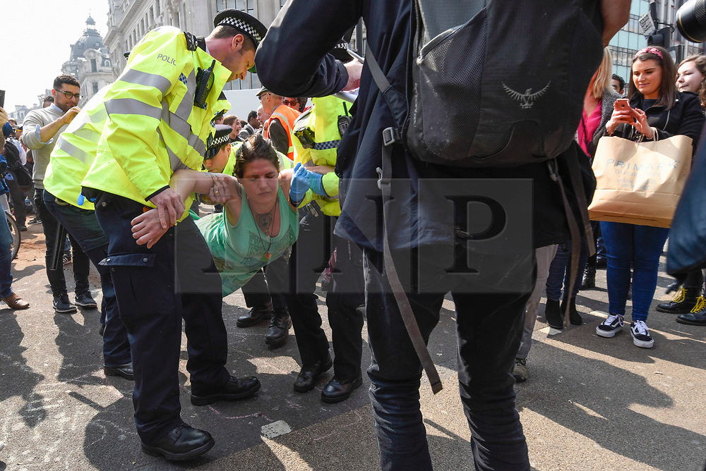 """© Licensed to London News Pictures. 17/04/2019. LONDON, UK.  Police officers arrest a protester at Oxford Circus during """"London: International Rebellion"""", on day three of a protest organised by Extinction Rebellion, demanding that governments take action against climate change.  Marble Arch, Oxford Circus, Piccadilly Circus, Waterloo Bridge and Parliament Square have been blocked by activists in the last three days.  Police have issued a section 14 order requiring protesters to convene at Marble Arch only so that the protest can continue.  Photo credit: Stephen Chung/LNP"""