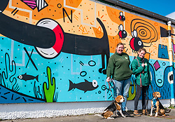 Pictured: Edinburgh Dog & Cat Home Mural Unveiling. , Edinburgh, Scotland, 03 May 2019. Beagles Bella (L) and Barney(R) with Vicky and Ceilidh from the rescue centre. Both dogs are looking for a good home. The 80 foot mural is unveiled today as a colourful addition to Seafield promenade. It is designed and painted by local artists Studio N_Name. It depicts the people, heritage and environment of the local community and features flora, fauna and historic elements of the local coastline. It has been made possible through through partnership with Edinburgh Shoreline Project. It is on the seafront wall of the dog & cat home which rescues, reunites and rehomes lost, stray and abandoned dogs and cats across Edinburgh and the Lothians, caring for 2,367 dogs and 771 cats in 2018.<br /> Sally Anderson | EdinburghElitemedia.co.uk