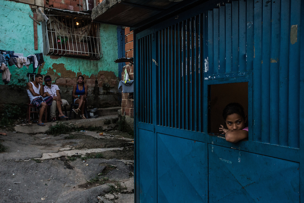 CARACAS, VENEZUELA - NOVEMBER 5, 2016: A  girl looks out of a window in Coche, a crime-ridden slum Caracas. A severe economic crisis in Venezuela, caused by the drop in oil prices and years of economic mismanagement under a Socialist government, has lead to an alarming rise in crime and insecurity in the country.  Hyperinflation has left both the working class and professional class of workers with salaries that cannot purchase enough food to feed their families. Many people are turning to crime to make ends meet.  PHOTO: Meridith Kohut for The New York Times
