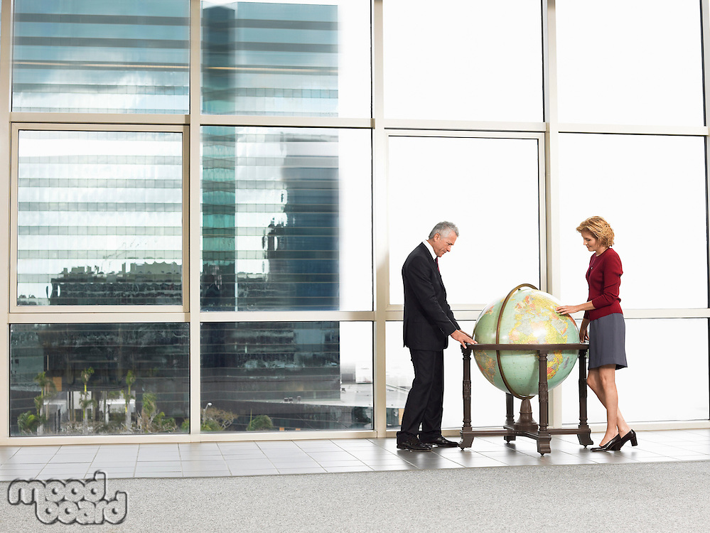Businessman and woman studying large globe in office