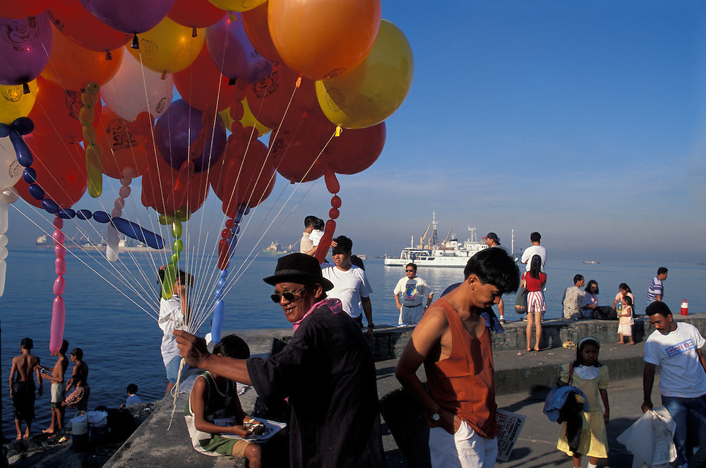 Philippines, Manila, Balloon seller and Sunday morning crowd at Rizal Park waterfront