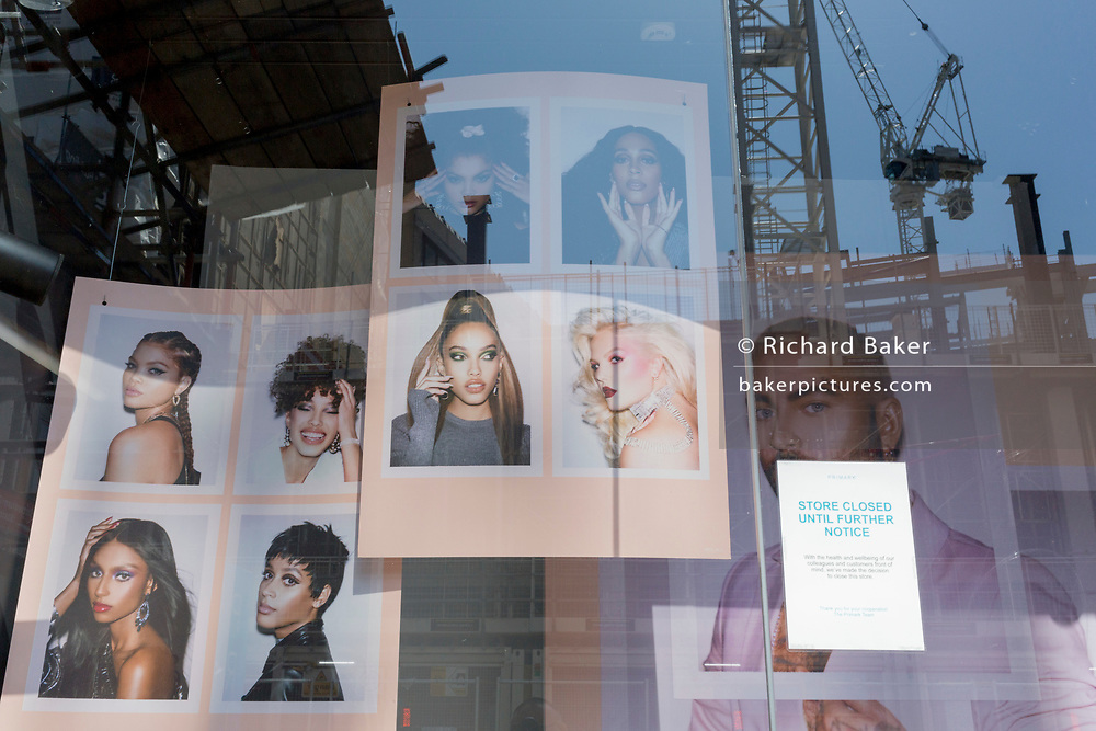 At the beginning of the fourth week of the UK government's lockdown during the Coronavirus pandemic, and with 120,067 UK reported cases with 16,060 deaths, construction cranes are idle above fashion mannequins in the window of budget retailer Primark stand in the brand's window on Oxford Street that would normally be a busy thoroughfare for shoppers and traffic and wich remains largely deserted at mid-day, on 20th April 2020, in London, England.