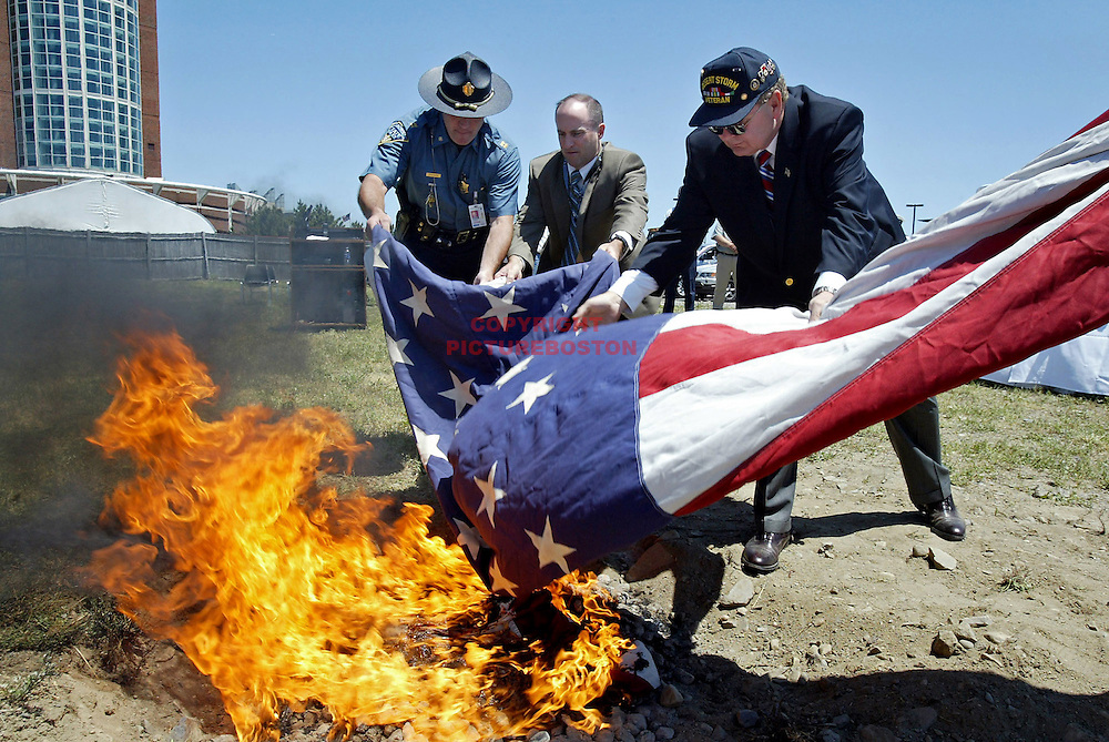 (06/13/08-Boston,MA) Flag retiring ceremony on the grounds of Logan Airport. More than 50 flags from across the state, including this huge flag that flew on the Tobin Bridge, were retired by burning. Here, from left, State Police Captain Daniel Risteen Jr, State Police Sgt Timothy Donnelly (CQ) and Dennis Treece, Massport Authority Director of Corporate Security throw the flag into the fire. .