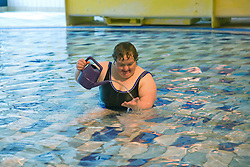 Day service user with learning disability playing with a watering can in the water at a local swimming pool,