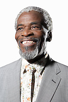 Happy senior man smiling while looking away against white background