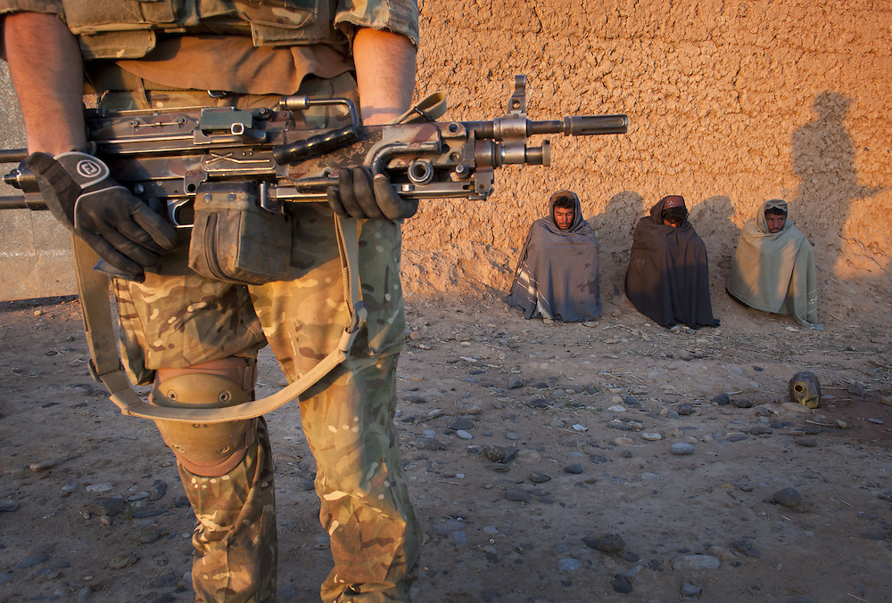 A British soldier of 16 Air Assault Bde's elite BRF (Brigade Reconnaissance Force) guards a group of local Afghan men as fellow soldiers search a compound for weapons and explosives during a dawn raid as part of an operation in the Western Dasht, Helmand Province, Southern Afghanistan on the 20th of March 2011.