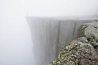 Person står i tåke på kanten av Preikestolen over Lysefjorden, Forsand, Rogaland.<br /> <br /> The Pulpit Rock 604 meters above the Lysefjorden covered in mist. Rogaland, Norway.