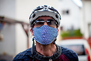 Portrait of a man wearing a face mask and a bicycle helmet in times of social distancing related to the spreading of the corona virus.