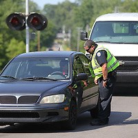 Jacob Whitlock asks a motorist for his driver's license duirng a checkpoint on Lumpkin Street.