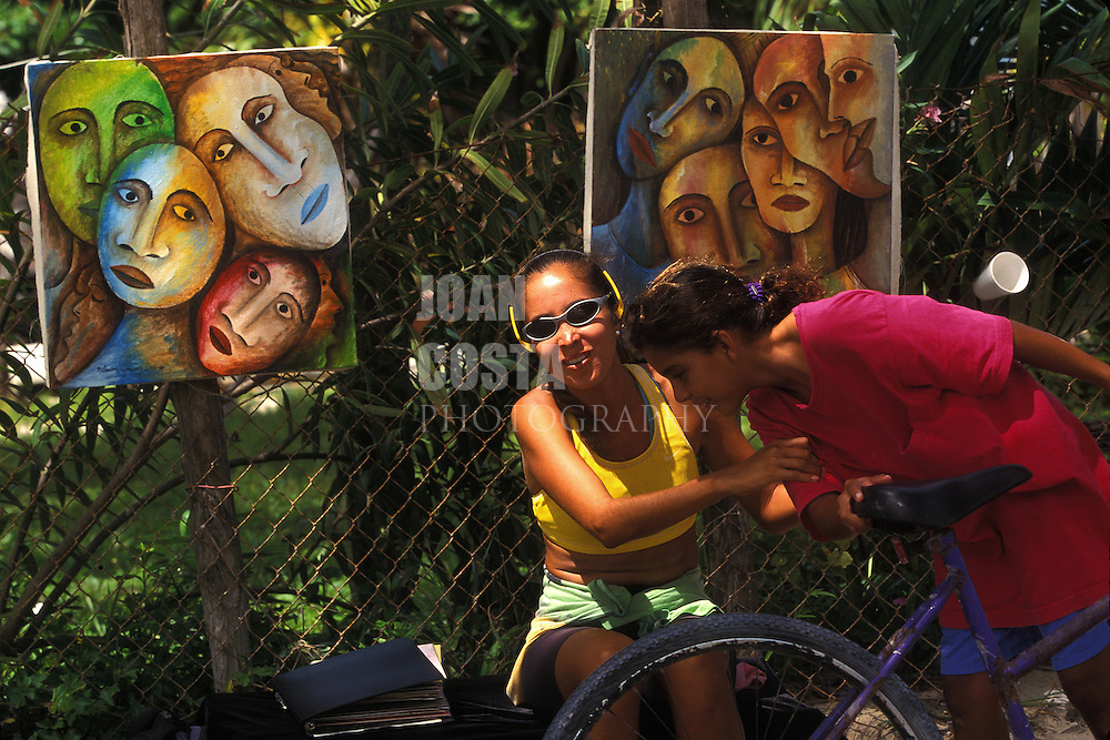BELIZE / San Pedro / Street painter showing her work of art...© JOAN COSTA