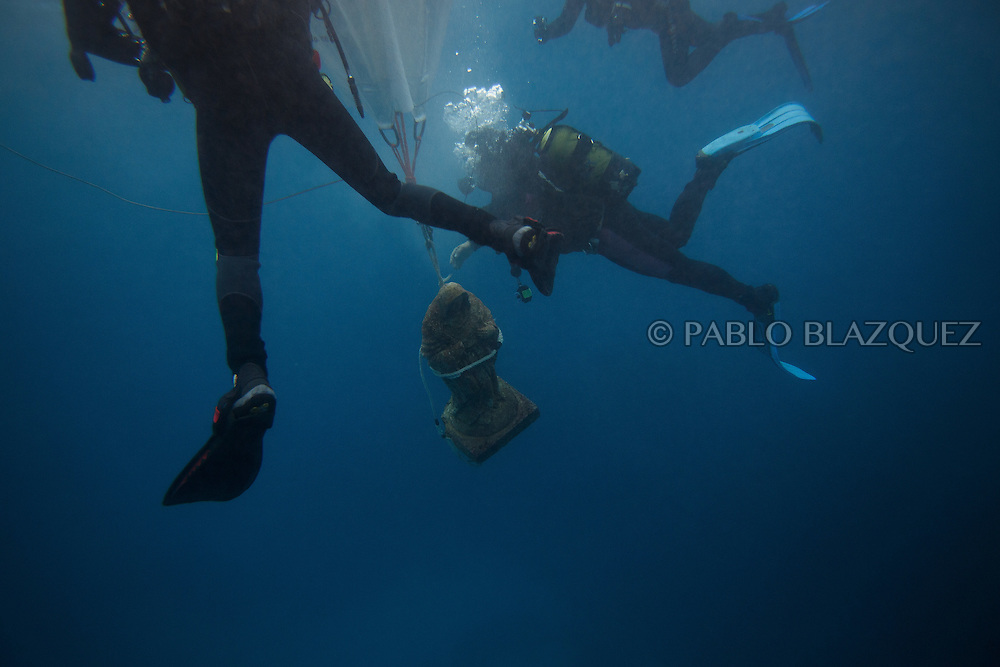 15/08/2016. Divers take an sculpture of the Virgin of Palm from deep sea to surface during the yearly Virgin of Palm maritime pilgrimage on August 15, 2016 in Algeciras, Spain. The Our Lady of Palm maritime pilgrimage in Algeciras dates back to 1975 and takes place annually when fishermen rescue the submerged virgin from the deep sea. Worshippers amid thousands of visitors await its arrival at the Rinconcillo beach. The devotion for the Virgin of Palm comes from the seventeenth century when a ship coming from Italy docked at Algeciras port to wait out bad weather. According to legend, once the crew of the ship removed a box with an image of the Virgin from its cargo the weather turned and the sea's tides were calmed. (© Pablo Blazquez)