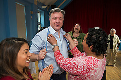 © London News Pictures. 01/05/2015. Shadow Chancellor ED BALLS  having his tie taken off and shirt opened by a group of older women during a visit to Kingsgate Community Centre in Kilburn, North London where Ed Balls took part in a line dancing session. Photo credit: Ben Cawthra/LNP
