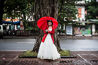 """A portrait of Le Thi Hang, a young bride in Hanoi, Vietnam. Nearly every day of the year, rain or shine, hot or cold, brides and grooms line up around the Sofitel Metropole hotel and its gardens to take engagement photographs to display at their weddings. Most couples go through an """"agency"""" that provides outfits, makeup, photographers, transport, and printed albums for a single, low price."""
