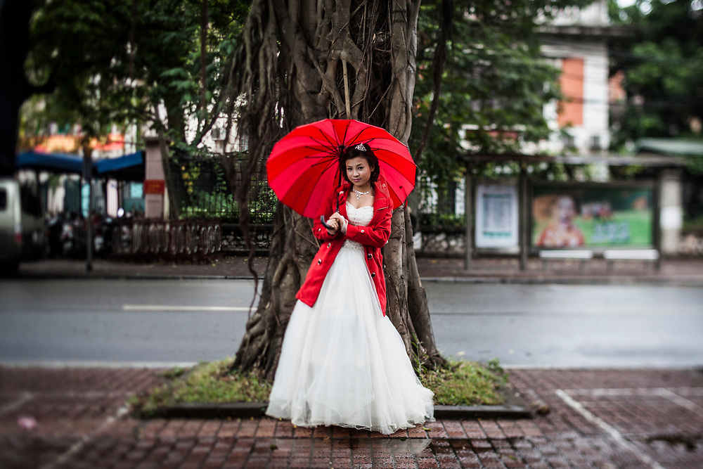 "A portrait of Le Thi Hang, a young bride in Hanoi, Vietnam. Nearly every day of the year, rain or shine, hot or cold, brides and grooms line up around the Sofitel Metropole hotel and its gardens to take engagement photographs to display at their weddings. Most couples go through an ""agency"" that provides outfits, makeup, photographers, transport, and printed albums for a single, low price."