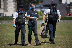 © Licensed to London News Pictures. 30/05/2020. London, UK. Police officers arrest a member of the environmental protest group Extinction Rebellion as they take part in a silent protest in Parliament Square calling for a citizens assembly to tackle the threat of COVID-19. Government has announced a series of measures to slowly ease lockdown, which was introduced to fight the spread of the COVID-19 strain of coronavirus. Photo credit: Ben Cawthra/LNP