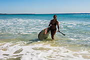 Young woman with a stand up paddle board, Cylinder Beach, North Stradbroke Island, Queensland, Australia