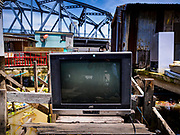 16 OCTOBER 2017 - BANGKOK, THAILAND:  A TV left in a home destroyed to make way for the city's plan to build a 14 kilometer long (22 mile) riverfront promenade. Thousands of families are expected to be evicted to accommodate the promenade. Krung Thon Bridge is in the background. The riverside communities, built on stilts over the water, are prone to flooding and the city has been trying to control them for years. The houses are the only affordable housing for available to some of the poorest people in Bangkok.          PHOTO BY JACK KURTZ