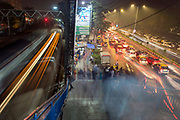 A slow shutter blur of trains, pedestrians and traffic in Mumbai, India