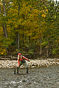 Woman smiling with catch while fly fishing on the Boise River during autumn, Idaho.