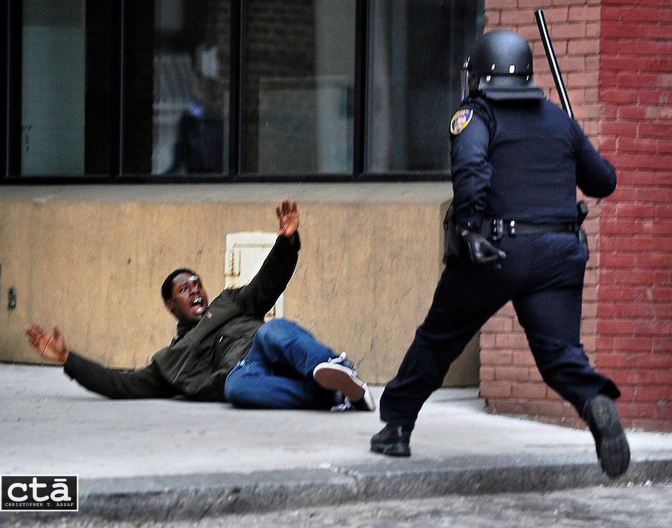"""A man screams """"Hands up!!"""" after being chased by a police officer in downtown Baltimore near Lexington Market. The man, who police suspected of looting and property damage, was running from police before he fell and was arrested. The looting and unrest April 27, 2015 followed the burial of Freddie Gray, who died while in police custody. Six officers were indicted in the case and trials are currently underway."""