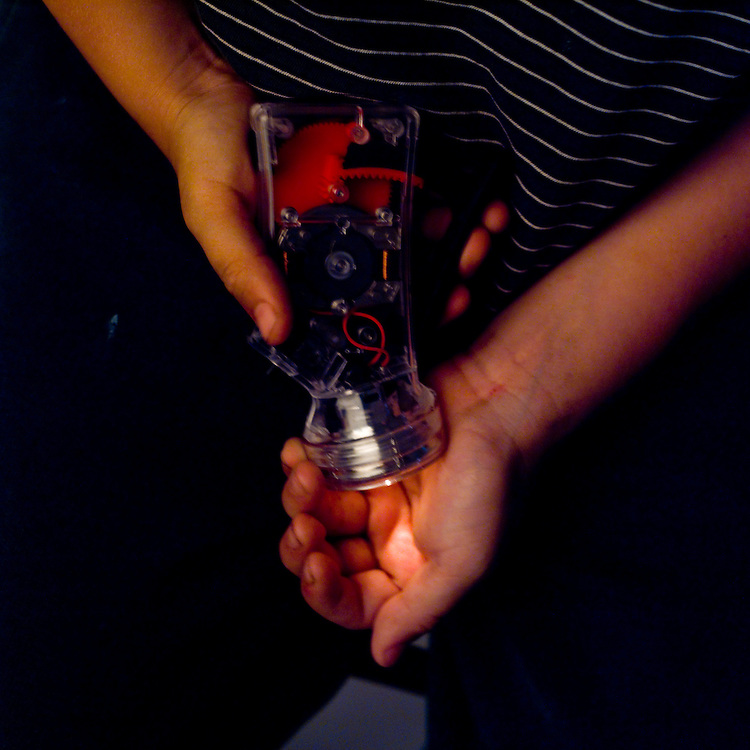 Light energy changing to electrical energy; using kinetic energy from chemical energy.  Boy pumps hand powered flashlight.