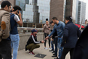 Passers-by are entertained by the three cup scam, on London Bridge, on 30th May 2018, in London, England.