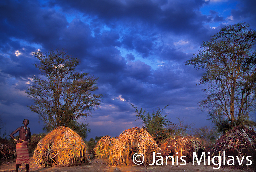Stormy sky over man standing next to grass huts of Mursi tribe village in Omo Valley Ethiopia, Africa.